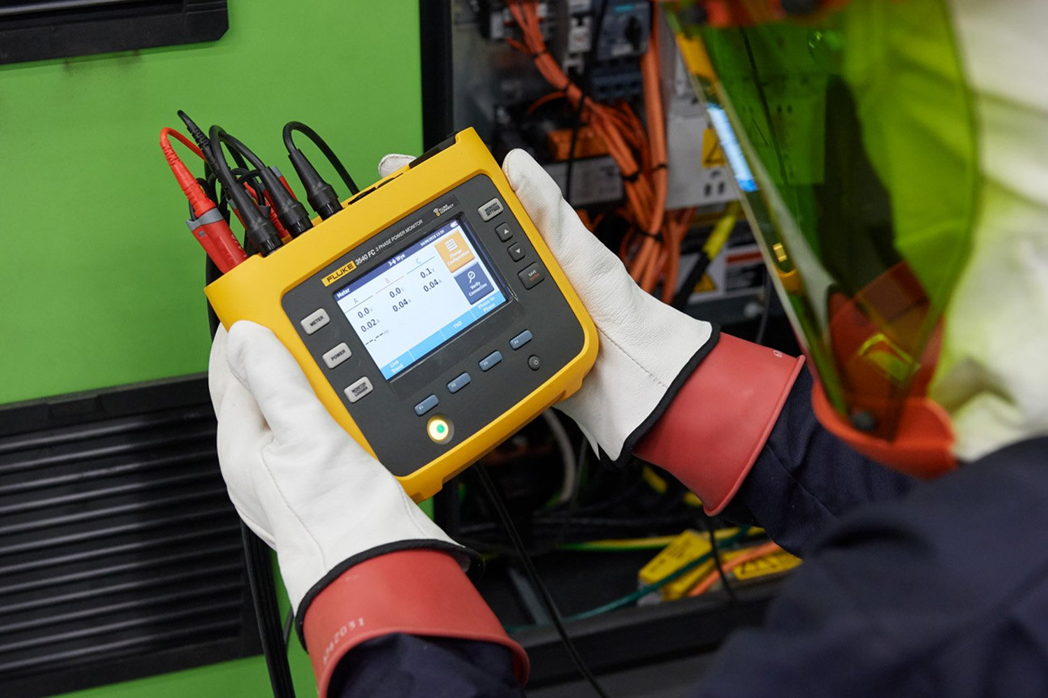 A clickable image of personnel using a Fluke 3540 FC Three-Phase Power Monitor. Leads to the power monitoring page.