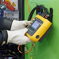 A user checks data on a Fluke 3540 FC Three-Phase Power Monitor.