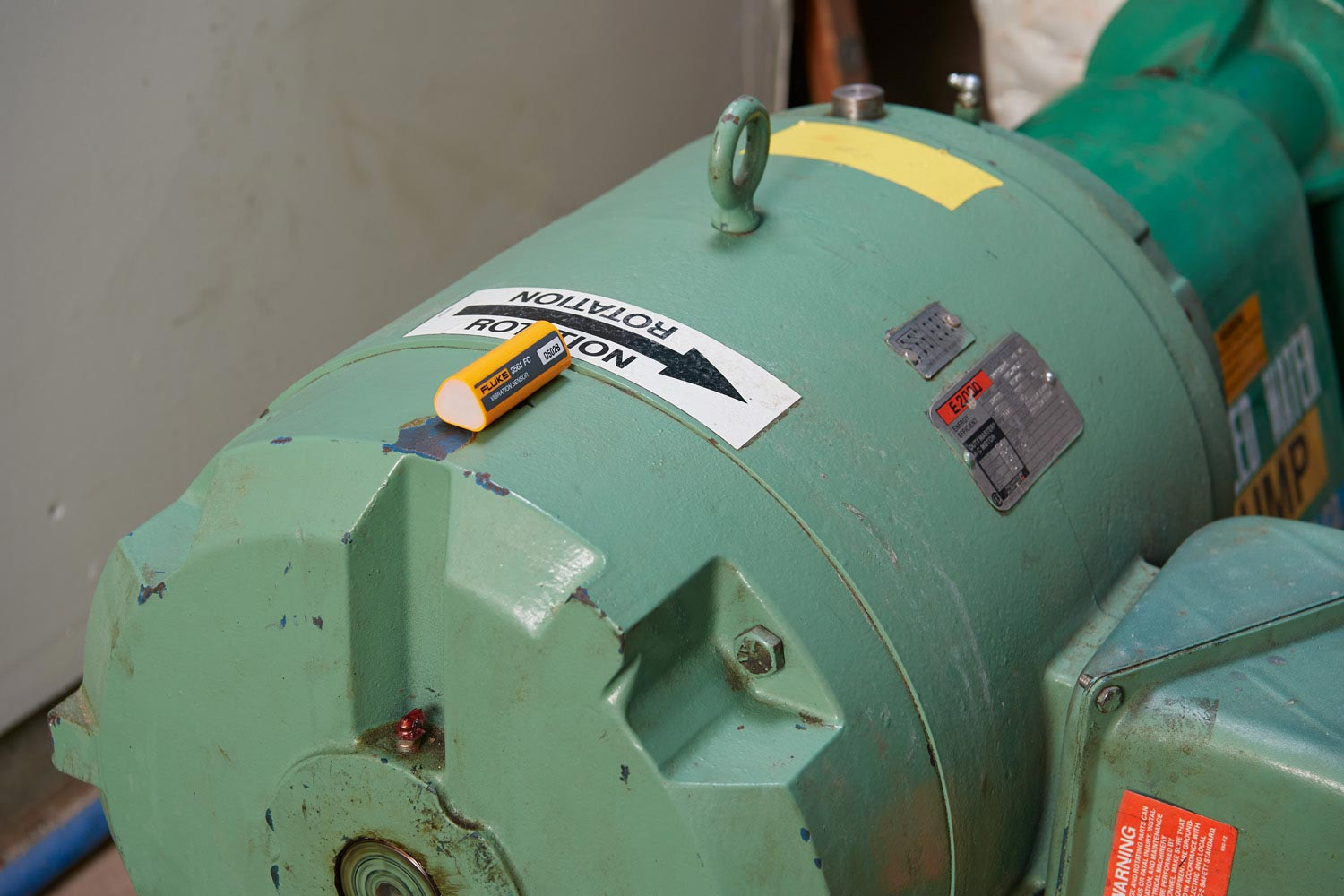 A Fluke 3561 FC Vibration Sensor is shown installed on a rotating asset.