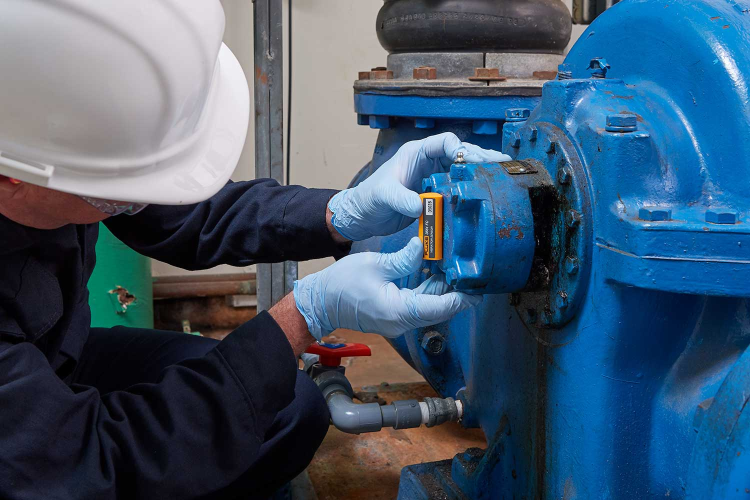 Personnel installing a Fluke 3561 FC Vibration Sensor on a rotating asset. vibration sensor applications