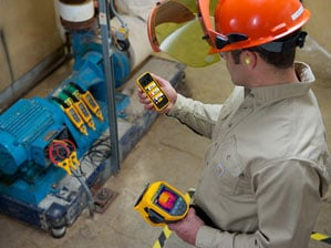 Technician reviewing measurements from Fluke Connect; tools on smartphone