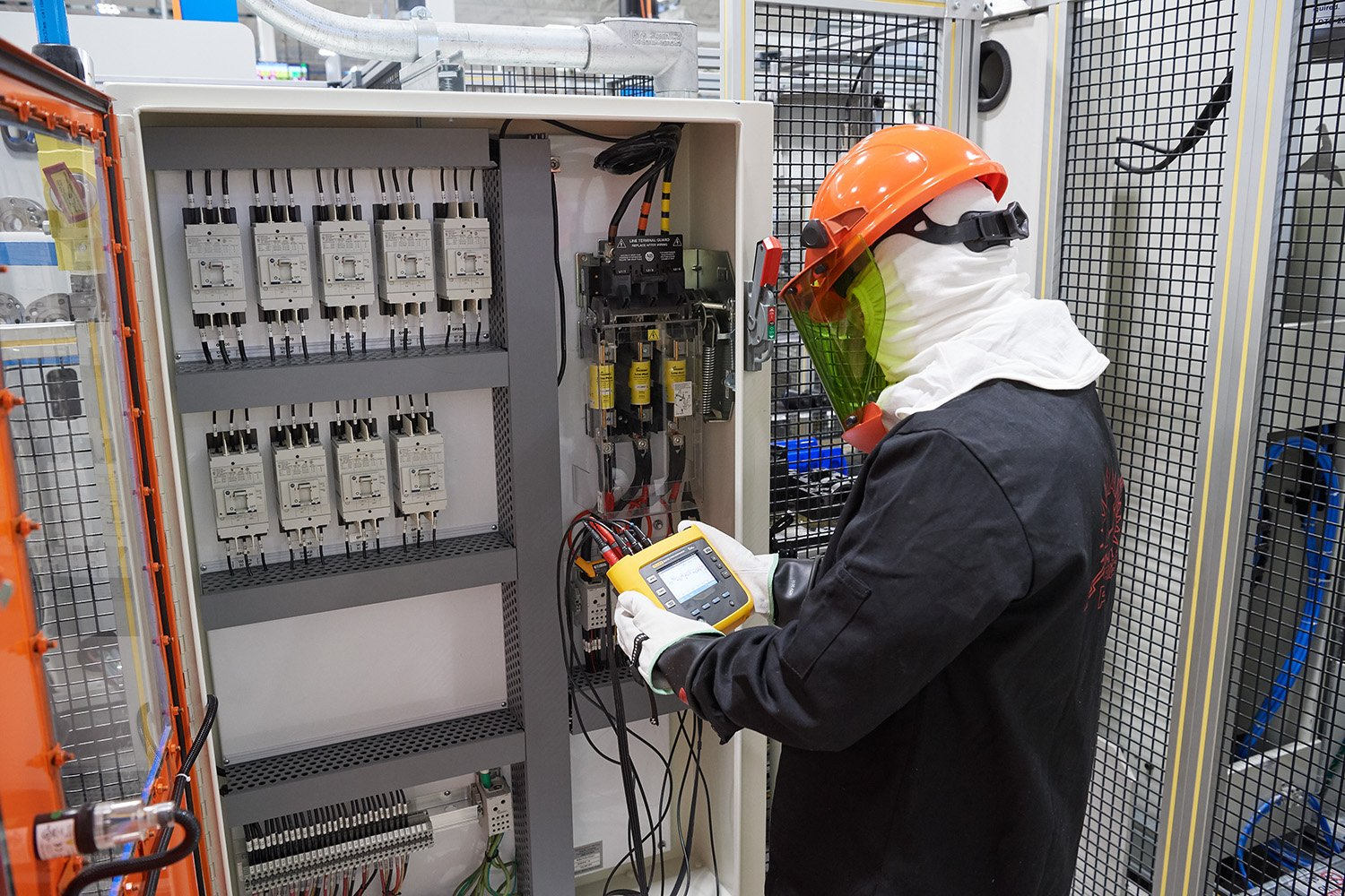 Dana technician sets up a power monitor within an electrical panel.