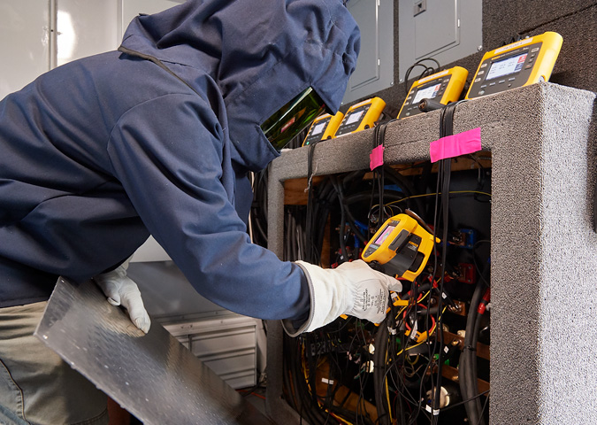 A UPS technician inspects the trailer's electrical panel with a Fluke Ti400 Infrared Camera.