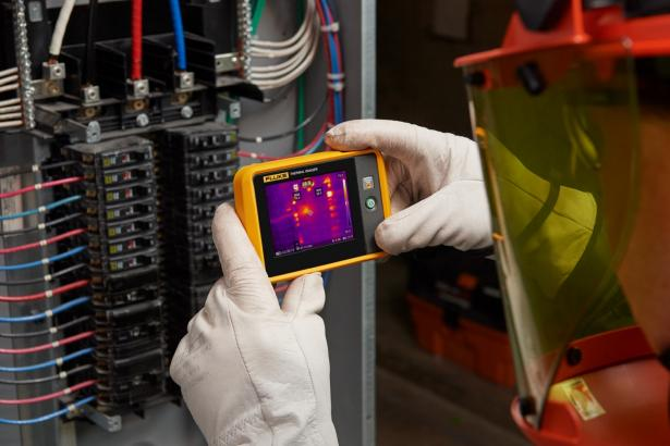 Pocket thermal imager used by man to scan circuit box